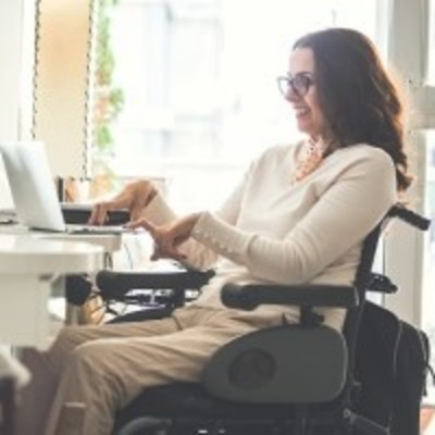 Woman in wheelchair typing on computer
