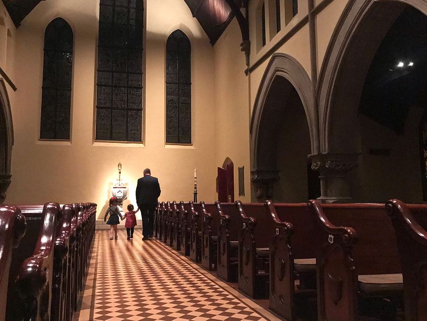 Adult and two children walking down the center aisle in a darkened, empty church