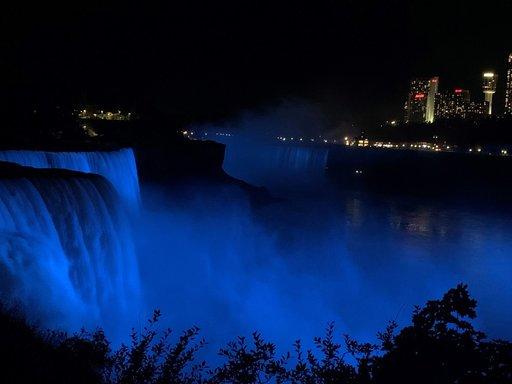 A photo of Niagara Falls lit with blue lights.