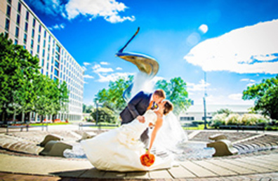 Married Creighton alumni kiss in front of the fountain