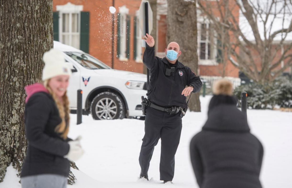 A university police officer trades snowball tosses with two students.