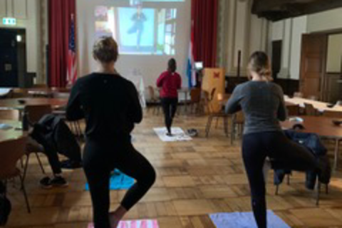 Students strike yoga poses as they face toward the instructor's screen on the wall