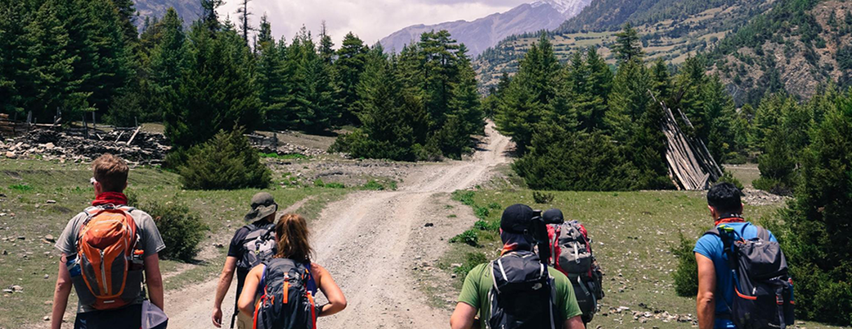 Students wearing backpacks hike along a path with distant mountains ahead of them