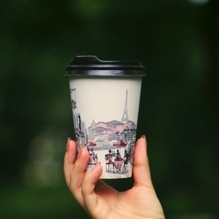 A hand holds up an internationally-themed to-go cup