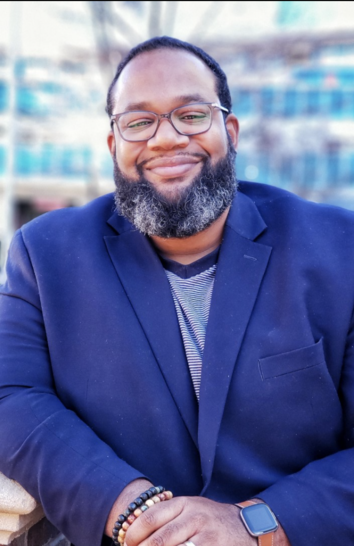 photo of smiling black male with beard and glasses and hands crossed wearing blue blazer