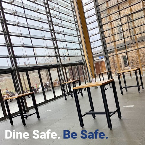 photo of high-top tables inside window-filled building