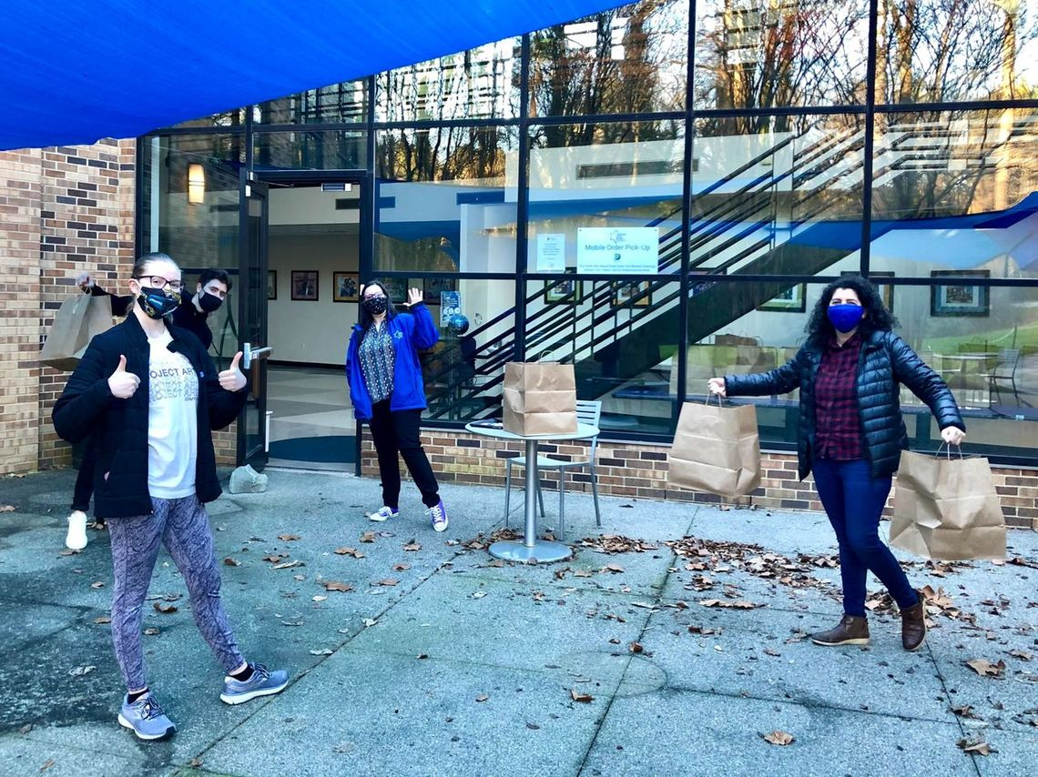 photo of students and staff picking up shabbat meals outside freeman center for jewish life