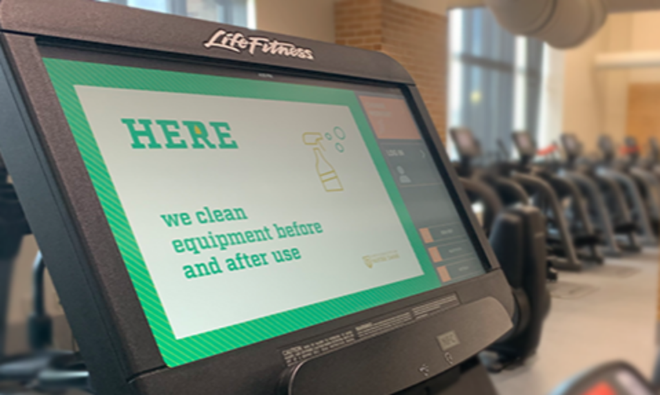 A screen on a piece of exercise equipment that reads Here we clean equipment before and after use