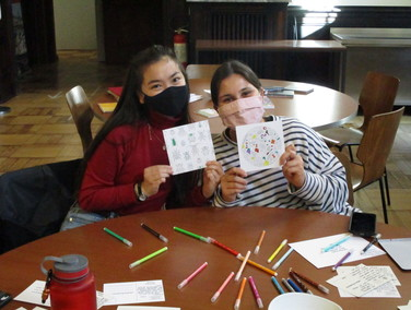2 masked students hold us their handmade valentines