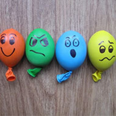 a line of multicolored stress balls with faces