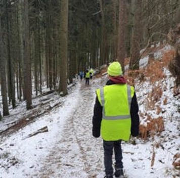 Person wearing fluorescent vest and hat walking on trail
