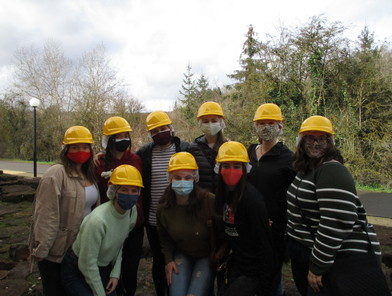 Masked MUDEC students wearing yellow hardhats