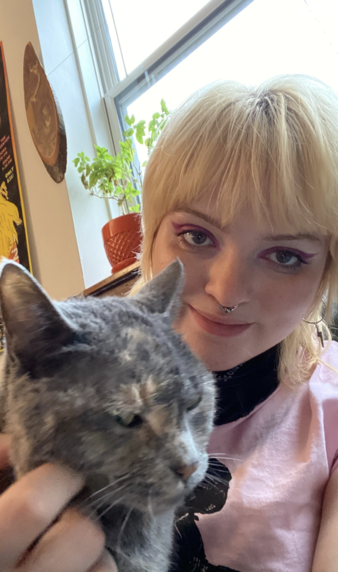 Greer, a young person with short bleached hair and pink, cat-eye makeup smiles at the camera while petting her cat, who gives the camera the side-eye.