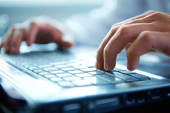 image of male hands typing on a laptop keyboard