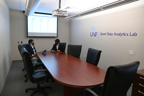 Dr. Choi and Dr. Kim sit at the conference table in the Sport Data Analaytics Lab