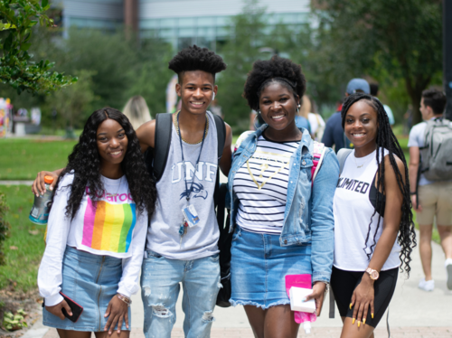 four UNF students pose for a photo outside of Market Days, pre-covid