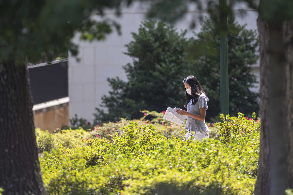 Masked student reading and walking across campus