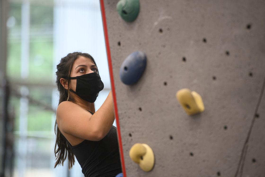 Masked student rock climbing