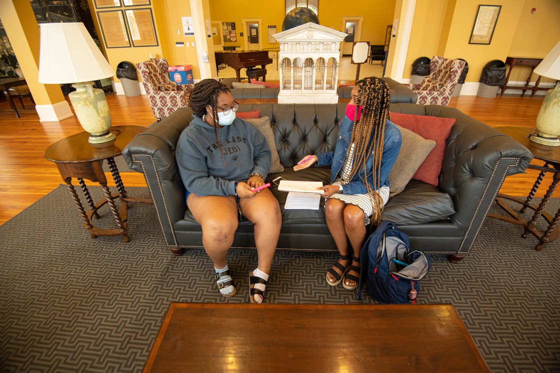 Photo of ttwo female students sitting on a sofa on campus wearing masks and talking