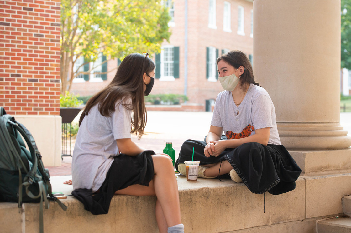 Photo of two masked students talking outdoors on campus