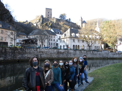 Masked students in a line along the river with buildings in background