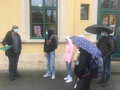 Guide speaks to umbrella-carrying students outside a building