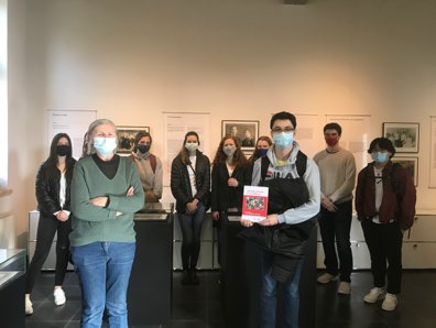 Students wearing masks in CMDH hold up a book and face camera