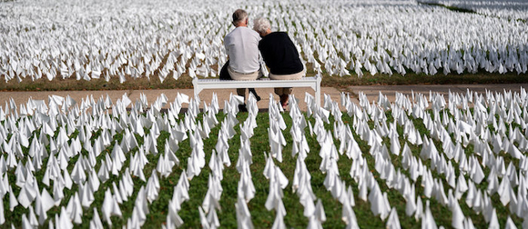 Two people sitting on a bench among a field of small white flags
