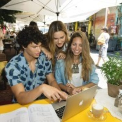 Students laughing aroud computer screen in Israeli souk