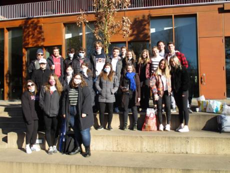 Masked students pose on steps