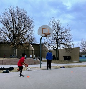 A teen in a red shirt preparing to shoot a basketball at a basket