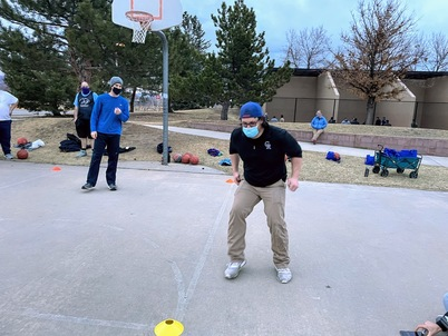 A man with a mask, black shirt, khaki pants and a blue hat attempt to run backwards on a basketball court