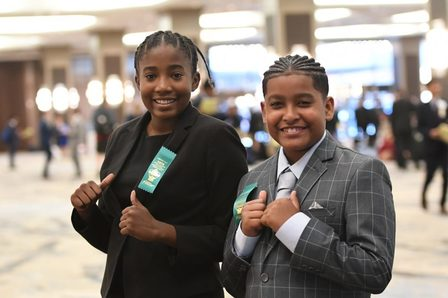 Two middle school students in suits point their thumbs toward their chests and smile