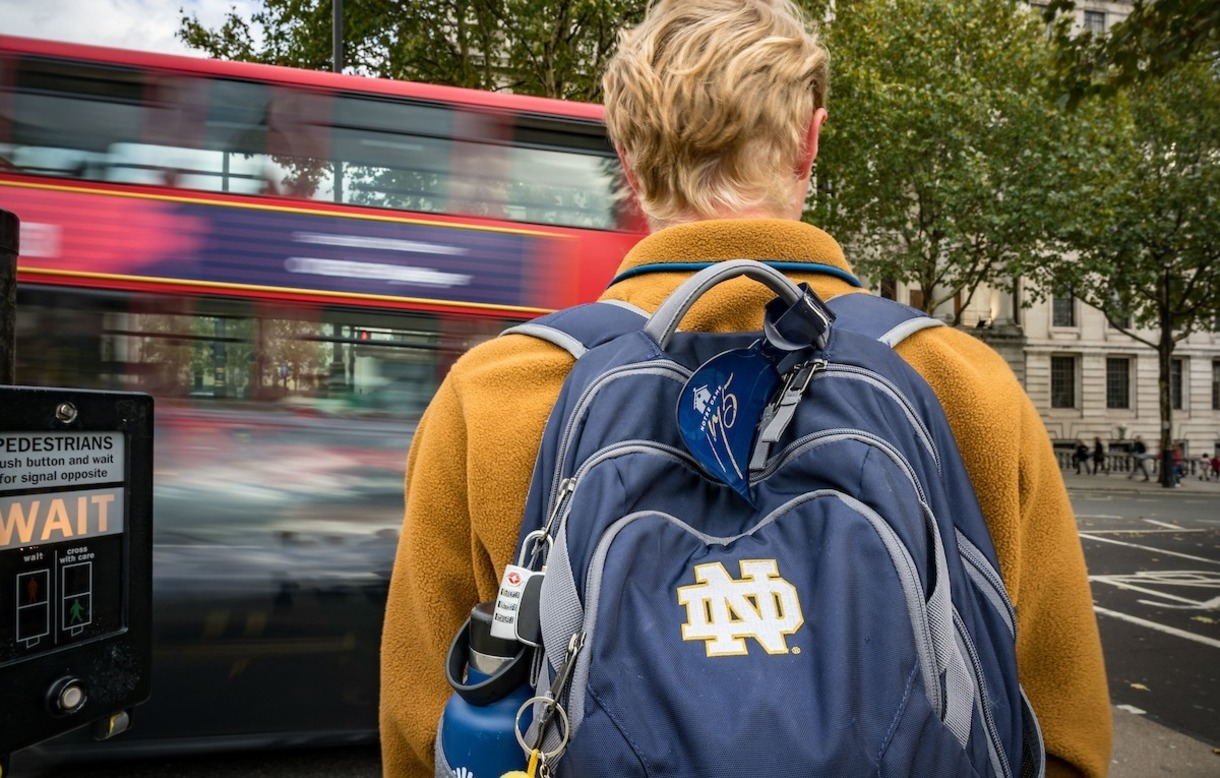 Photo of student wearing Notre Dame backpack isstanding on a corner in Europe as bus drives by.