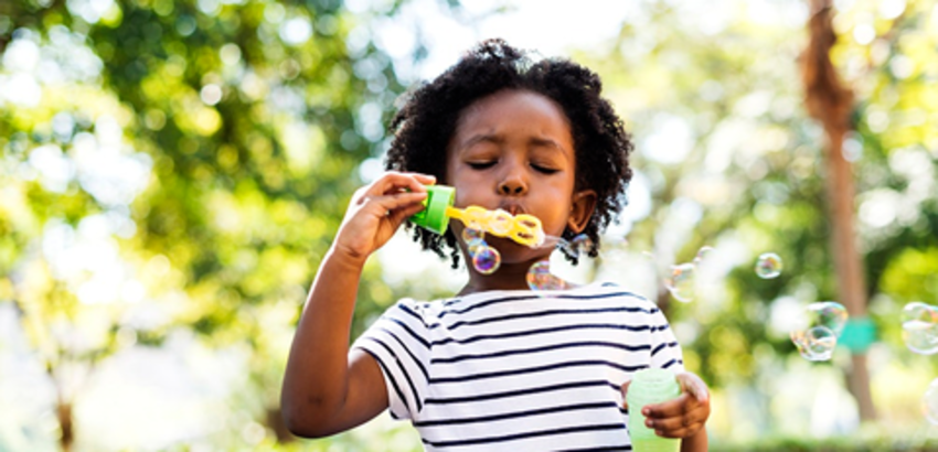 Girl blowing bubbles outside, article on learning outside