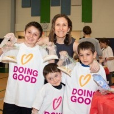 Family smiling in Good Deeds Day shirt from last year