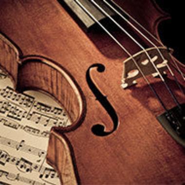 detail of violin resting on sheet music