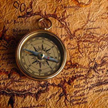 old-fashioned compass resting on old map