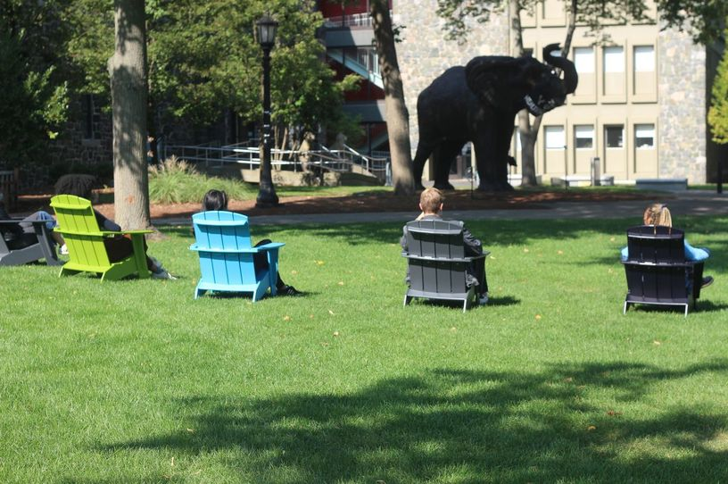 Students sitting socially-distantly in Adirondack chairs on Academic Quad across from Barnum Hall