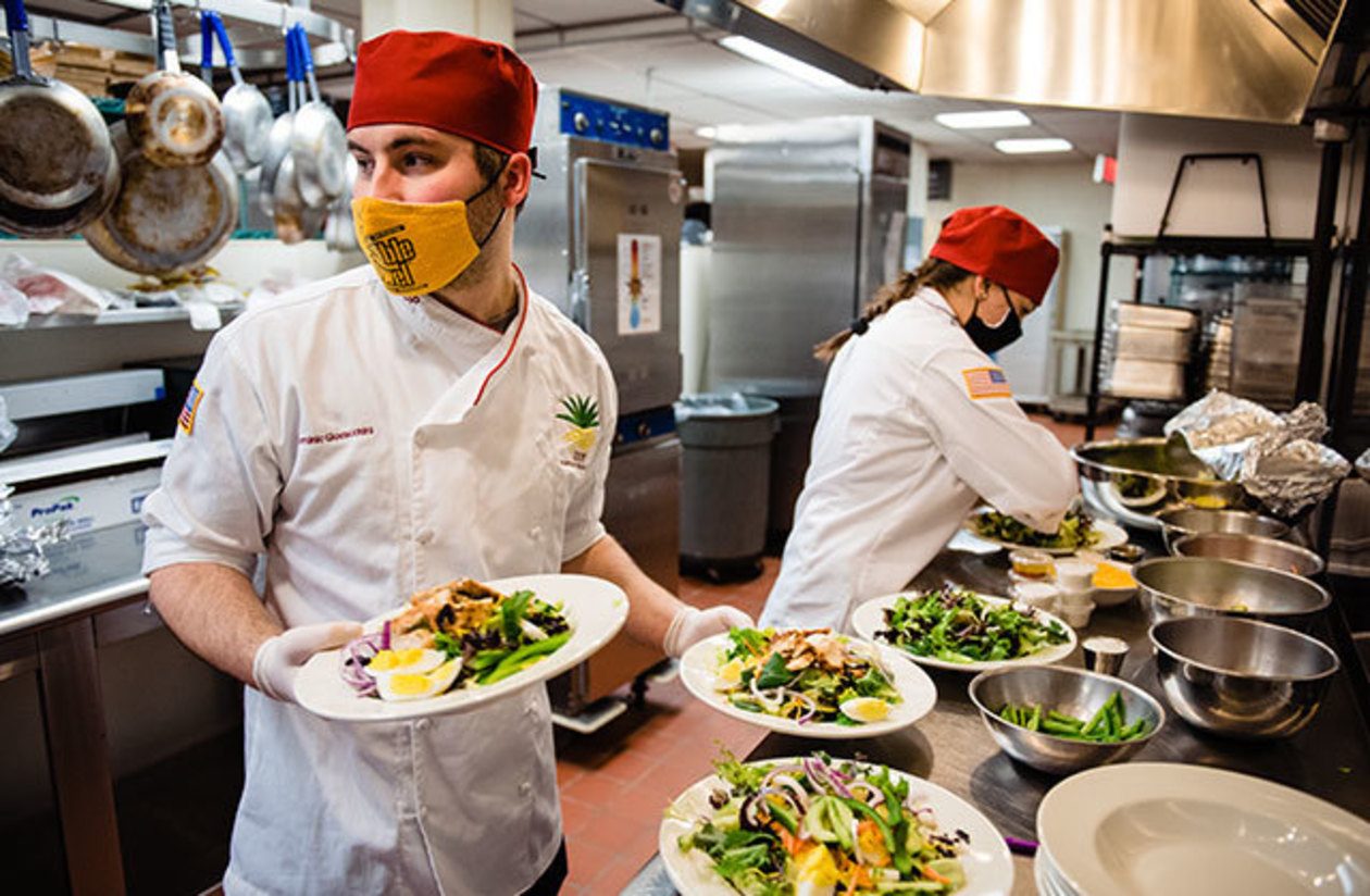 two students preparing several salads in the Allenwood kitchen