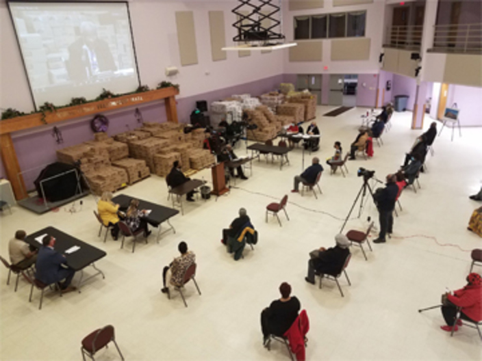 Attendees of the community meeting sitt six feet apart. watching a presentation on a jumbo screen.ing