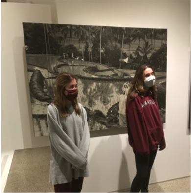 Students pose in front of an artwork