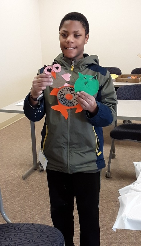 4-H Member holding up his CD art projects