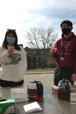 Two masked students hold cups of tea with the selections visible in foreground