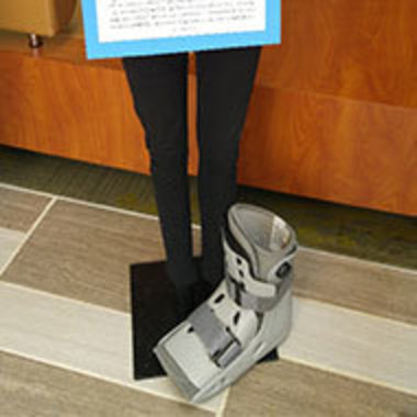 """display from previous """"What Were You Wearing?"""" exhibit showing black pants and a medical walking boot"""