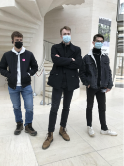 Three masked students at the art exhibit