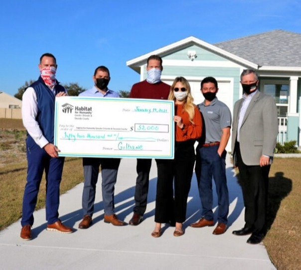six people stand with check made out to Habitat Orlando & Osceola