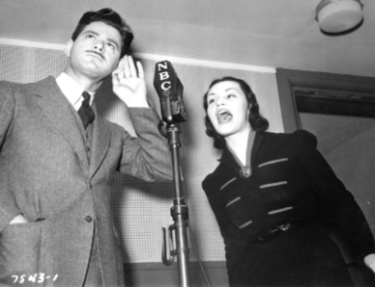 "Norman Corwin and actress Peggy Burt on the ""Magic Key of RCA"" program. Circa late 1930s."