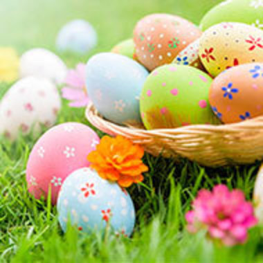basket of decorated eggs sitting in the grass