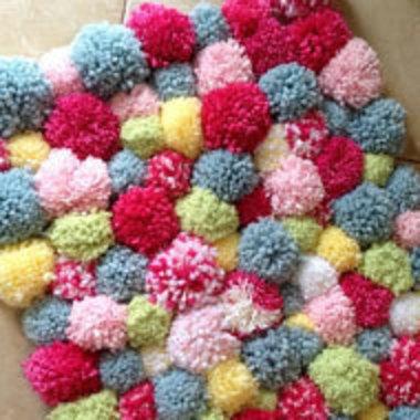 multicolored pom-pom rug